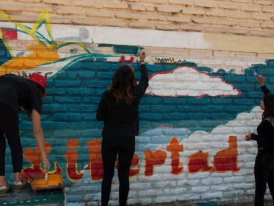 Estudiantes beneficiarios del programa Actuar a Tiempo pintan mural en su colegio